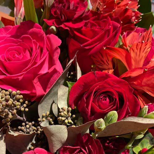bouquet of red roses, red alstroemerias, eucalyptus, red hypericums and more.