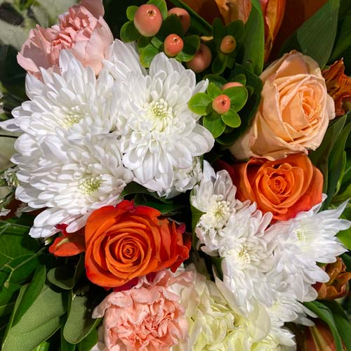 bouquet of Peach Carnations, Orange Roses, White Pom Cushions, White Hydrangeas and more.